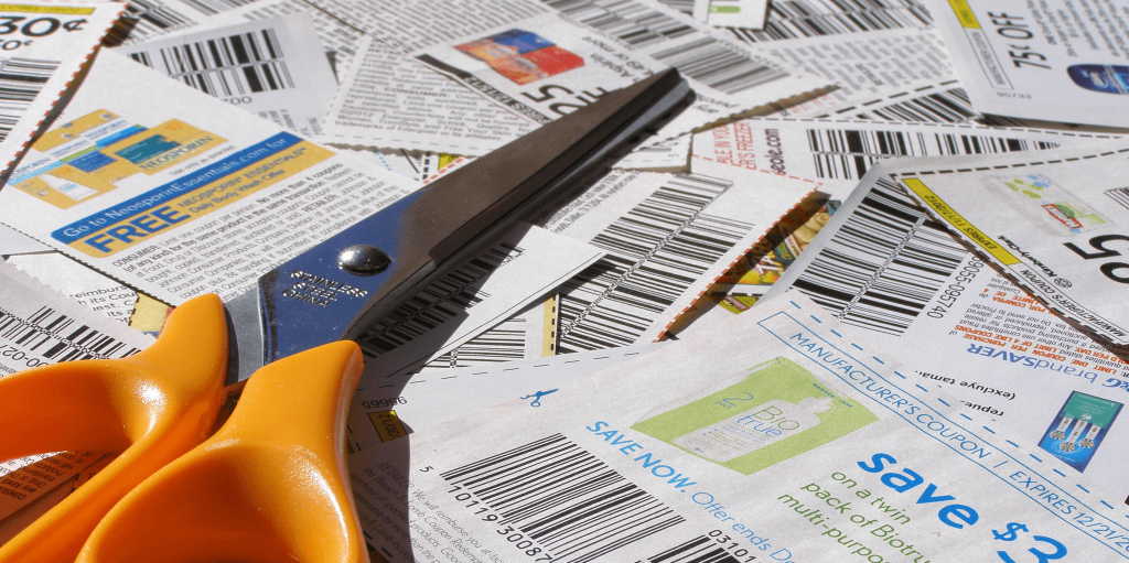 Coupons in a pile with scissors.